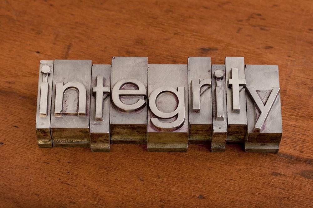 integrity word in vintage, metal letterpress printing blocks on scratched wooden background
